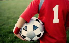 joueur de foot avec un ballon sous le bras